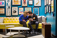 "Doug Robinson plays guitar while Allie Ruane listens in the lobby of The Verb Hotel in the Fenway neighborhood of Boston, Massachusetts, USA, on Friday, Dec. 4, 2015. The hotel is considered a ""boutique hotel"" and has collections on display throughout the premises of music memorabilia from the Boston area. On the wall of hotel lobby hang pieces of the memorabilia collection of Boston-area rock historian David Bieber."