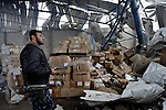 A Hamas police officer inspects damaged materials inside a pharmaceutical warehouse in the Jabalya refugee camp that was hit during February 9, 2011, airstrikes by U.S.-made Israeli war planes. The bombings, which the Israeli military claimed came in response to rocket attacks from inside Gaza, injured eight people..