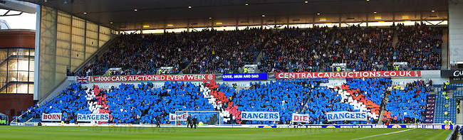 Rangers fans in the Broomloan Road stand with a card display