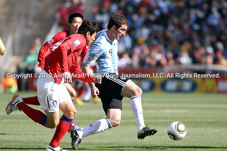 17 JUN 2010:  Gonzalo Higuain (ARG)(9) moves the ball past two South Korean players.  Higuain scored a rare three goal hat trick during this match.  The Argentina National Team defeated the South Korea National Team 4-1 at Soccer City Stadium in Johannesburg, South Africa in a 2010 FIFA World Cup Group E match.