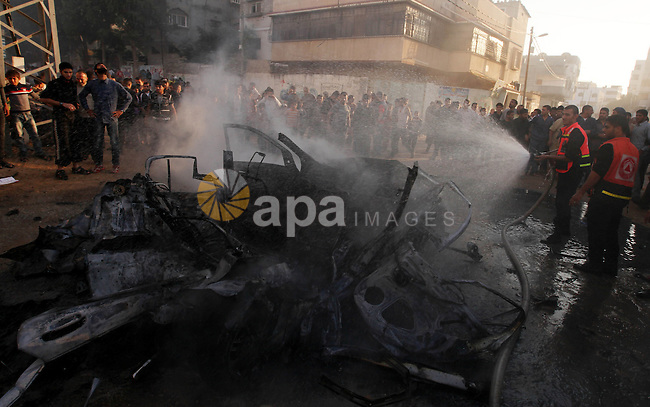 """Palestinian firefighters extinguish fire from a vehicle following an Israeli strike in Gaza City on November 20, 2012. Israel's air force dropped leaflets across several districts of Gaza City urging people to evacuate their homes """"immediately"""" amid fears of an imminent ground invasion. Photo by Majdi Fathi"""