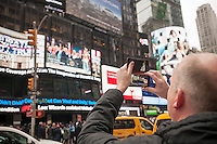 Visitors to Times Square in New York view the inauguration of Donald Trump as the 45th president of the United States on ABC television's giant screen on Friday, January 20, 2017.   (© Richard B. Levine)