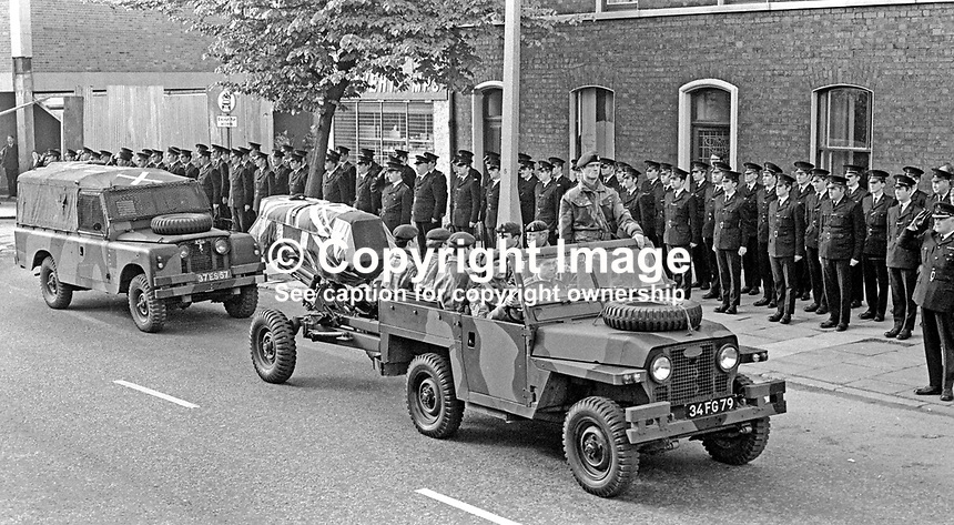 Members of the RUC line up in a guard of honour as the Union Jack draped coffin of Sergeant Michael Willets on a gun carriage passes Springfield Road Police Station. The paratrooper who died on 25th May 1971 used his body to shield 2 children from a bomb lobbed into police station. His spontaneous act of courage earned him a postumous George Cross. 197105280208a.<br />