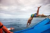 INDONESIA, Mentawai Islands, Kandui Surf Resort, surfer diving off of a boat into the Indian Ocean, Bankvaults