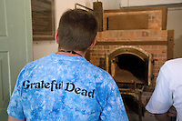 "Germany. Bayern state. The Dachau Concentration Camp Memorial Site. A young american boy, wearing a t-shirt of the music band ""The Grateful Dead"", stands in front of one  the four ovens in the crematorium, the barrack X. .Still preserved today are the first crematorium built in 1940 and the so-called barrack X, built in 1942/43. The crematorium was used to dispose of the corpses from the concentration camp; the ovens were mostly in operation around the clock. On march 22, 1933, the first concentration camp was opened in Dachau by the Nazis. It became a model for all later concentration camps established under the control of the SS men and the Third  Reich. © 2007 Didier Ruef"