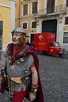 Roma, 01 Aprile 2017<br /> Un uomo vestito da centurione romano passa davanti un APE con i colori e simboli della A.S. Roma