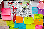"""07 MAY 2010 - BANGKOK, THAILAND: Notes left by the Red Shirts on a wall in Ratchaprasong Intersection call for Thai Prime Minsiter Abhisit Vjjajiva to step down frame a caricature of the Prime Minister as Hitler with Thai blood coming off his hands. Red Shirt protestors in Ratchaprasong intersection, Friday May 7, more than one month after the Reds occupied the intersection. Members of the United Front of Democracy Against Dictatorship (UDD), also known as the """"Red Shirts"""" and their supporters moved their anti government protests into central Bangkok Apr. 4 when they occupied Ratchaprasong intersection, the site of Bangkok's fanciest shopping malls and several 5 star hotels. The Red Shirts are demanding the resignation of current Thai Prime Minister Abhisit Vejjajiva and his government. The protest is a continuation of protests the Red Shirts have been holding across Thailand. They support former Prime Minister Thaksin Shinawatra, who was deposed in a coup in 2006 and went into exile rather than go to prison after being convicted on corruption charges. Thaksin is still enormously popular in rural Thailand. This move, away from their traditional protest site in the old part of Bangkok, has gridlocked the center of the city and closed hundreds of stores and restaurants and several religious shrines.     PHOTO BY JACK KURTZ"""