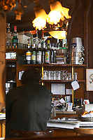 A man in a black shirt sitting at the bar reading a newspaper paper and drinking. Shelves with bottles, glasses and ice buckets. The Bistrot du Peintre is an old fashioned Paris café cafe bar restaurant of art nouveau design with polished brass, mirrors and old signs