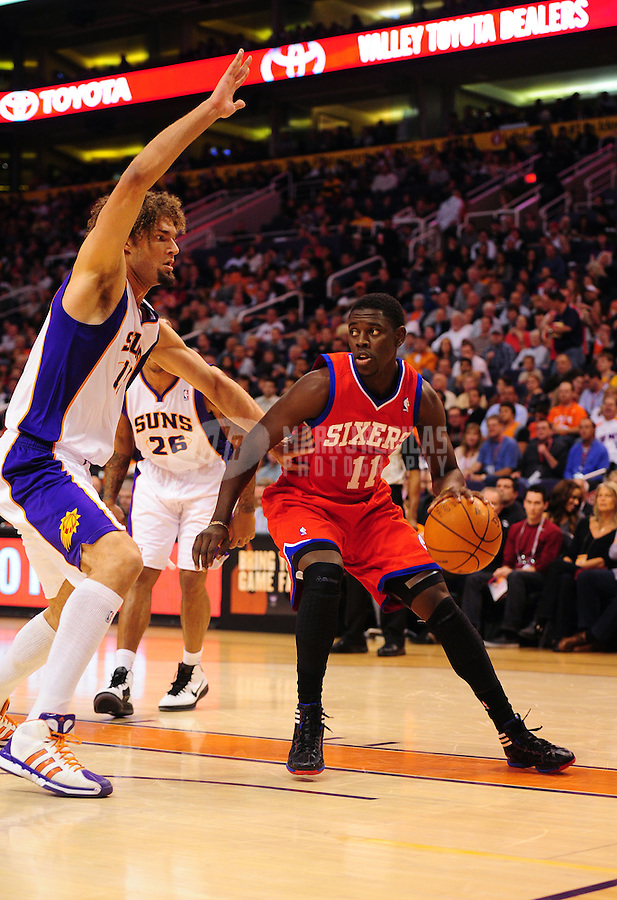 Dec. 28, 2011; Phoenix, AZ, USA; Philadelphia 76ers guard Jrue Holiday (11) drives to the basket against Phoenix Suns center Robin Lopez at the US Airways Center. The 76ers defeated the Suns 103-83. Mandatory Credit: Mark J. Rebilas-USA TODAY Sports