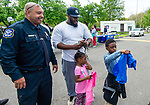 WATERBURY,  CT-051519JS12-Waterbury police officer Querino Maia talks with Waterbury resident Tyrell Williams while Tyrell's children Mekhi Williams, 7, and Ryleigh Williams, 3, check out tee shirts given to them by Lacey Rodrigues of PAL, during the Waterbury Police Community Outreach Program Wednesday at Waterville Park in Waterbury. The event was hosted by the Waterbury police department and town departments who were on hand to meet residents and offer assistance or answer any questions they may have. <br /> Jim Shannon Republican American