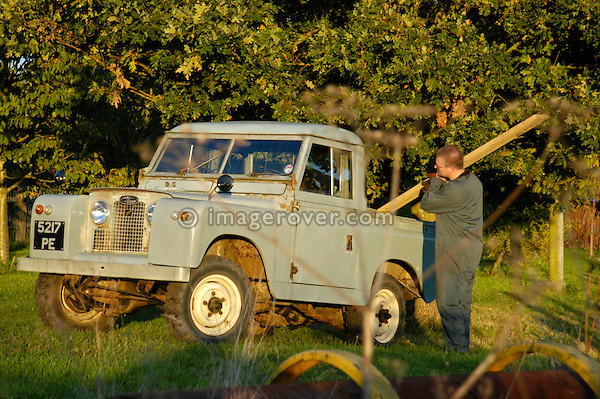 Workman in overall loading a timber beam into the back of a historic 1963 Landrover Series 2a truckcab in very original and full working condition on a farm in Dunsfold, UK 2004. --- RELEASES AVAILABLE FOR CERTAIN USES. Automotive trademarks are the property of the trademark holder, authorization may be needed for some uses.