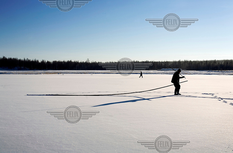 Fishermen fish in a frozen lake at the Bedime village in Yakutia.