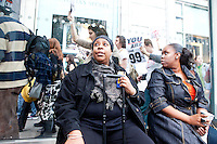 "Chez Brown and her mother Tina wait for their bus and watch as thousands of people march up 6th Avenue to Times Square on October 15, 2011 in New York City in support of the ""Occupy Wall Street"" movement."