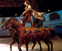 Julien Beaugnon performs stunts while Roman riding, standing atop a pair of horses with one foot on each horse.