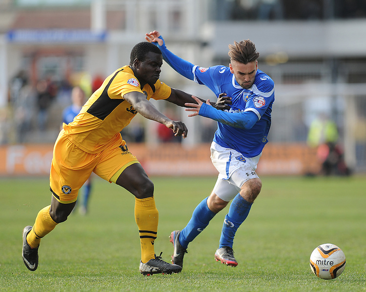 Newport County's Ismail Yakubu vies for possession with Portsmouth's Ricky Holmes<br /> <br /> Photo by Ashley Crowden/CameraSport<br /> <br /> Football - The Football League Sky Bet League Two - Newport County AFC v Portsmouth - Saturday 29th March 2014 - Rodney Parade - Newport<br /> <br /> &copy; CameraSport - 43 Linden Ave. Countesthorpe. Leicester. England. LE8 5PG - Tel: +44 (0) 116 277 4147 - admin@camerasport.com - www.camerasport.com