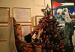 A Palestinian woman wearing traditional clothes decorates a Christmas tree inside the municipality building in the West Bank city of Bethlehem on December 15, 2009. Christians Pilgrims and tourists are expected to visit Bethlehem, the alleged birthplace of Jesus Christ, this coming Christmas. According to the Christmas story, the three Kings who visited Jesus Christ in Bethlehem followed a star until they found him in a manger in this now holy town. Photo by Najeh Hashlamoun