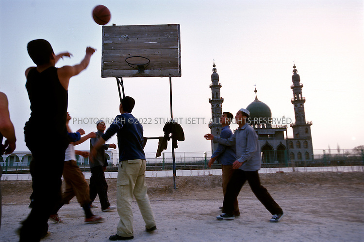 3/14/2004--Hong Gangzi, Ningxia Province, China..Youngs students at the Hong Gangzi Mosque play basketball at sunset. The mosque is for the Hufuye muslim sect led by Sheik Hong Yang (39) in China's arid Ningxia Province...With nearly a million members, the Hufuye sect is one of many religious groups expanding under greater religious freedoms in China although most still fear government crackdowns and follow Beijing's line...Photograph by Stuart Isett     .©2004 Stuart Isett. All rights reserved
