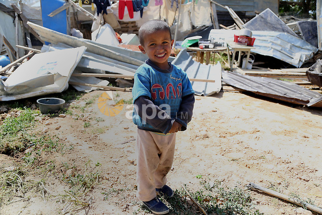 A child from the Arab Jahalin Bedouin community walks past the debris of homes in the West Bank Bedouin camp of al-Khan al-Ahmar on April 7, 2016 after Israeli authorities demolished four houses that they said were built without permission. Photo by Hamza Shalash