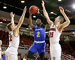 VERMILLION, SD - JANUARY 24: Tevin King #2 from South Dakota State University takes the ball to the basket between Tyler Peterson #22 and Tyler Hagedorn #25 from the University of South Dakota during their game Wednesday night at the Sanford Coyote Sports Center in Vermillion, SD. (Photo by Dave Eggen/Inertia)