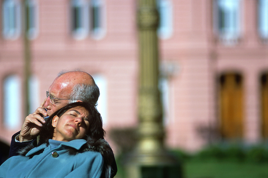 A porteno couple basks in the sun in front of the Casa Rosada, Argentina's presidential palace, in Buenos Aires.