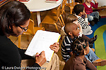 Education preschool 3-4 year olds female teacher sitting and taking notes observing children participating in circle time horizontal