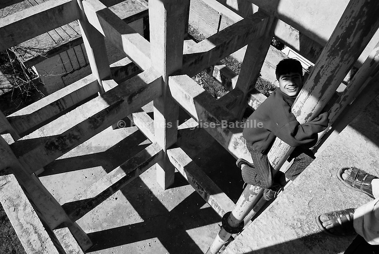 A kid slides down from the top of an abandoned water tower in Rawalpindi, Pakistan.