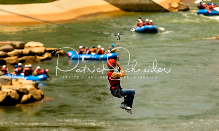 Participants take flight, zooming through the air over the US National Whitewater Center (USNWC) on the USNWC's zip-lines, part of the facilities high-adventure offerings. The popular outdoor adventure activity lets outdoor enthusiasts be secured into a harness then propelled by gravity along an inclined steel cable. Charlotte, North Carolina's US National Whitewater Center offers two zip lines, which vary in height and distance traveled, as well as one of the largest outdoor climbing facilities in the world. The USNWC is a non-profit outdoor recreation facility open to the public for whitewater rafting, kayaking, canoeing, rappelling, zip lining, mountain biking, hiking, climbing and more. The center opened to the public in 2006.