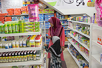 January 15, 2015 - Rawang (Malaysia). Mardiona Hakim, wife no 4 of Global Ikhwan's CEO, shops at the company's clinic with one of her daughters. The company has a series of own products such as soap, shampoo, tooth paste, water and sodas. © Thomas Cristofoletti / Ruom