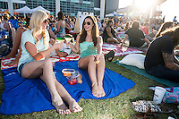 Two attractive females Austinites enjoy margaritas on the lawn at a popular Austin weekly summertime live music and movies event.