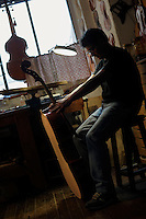 "Il maestro Carlos Roberts, liutaio del Consorzio Liutai ""Antonio Stradivari"", mentre costruisce un  violoncello nel suo laboratorio. .The master Carlos Roberts while building a cello in his laboratory.The Consortium of Violinmakers.."