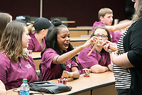 MSU Veterinary Camp participants, from left to right, Emily Foppe, Kaylondria Thomas and Lanie Sutherland are introduced to a snake by College of Veterinary Medicine Clinical Instructor Christine Calder. The camp is designed for students who have aspirations of working as a veterinarian, becoming a scientist or working in an animal-focused career.<br />