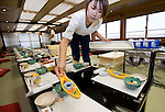 "A staffer sets the tables in readiness for an evening of entertainment aboard a ""Yakata-bune"" pleasure boat run by the Harumiya Co. in Tokyo, Japan on 31 August  2010. Photographer: Robert Gilhooly"
