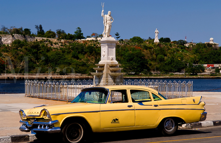 Classic Dodge 50s auto in front of river and statues with Christ statue on hill in background in Havana Cuba Habana