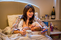 "A woman breastfeeding 5 month old twins at the same time on her bed in her bedroom while drinking a cup of tea and texting on her mobile phone.<br /> <br /> Image from the ""We Do It In Public"" documentary photography project collection: <br />  www.breastfeedinginpublic.co.uk<br /> <br /> Hampshire, England, UK<br /> 11/02/2013"