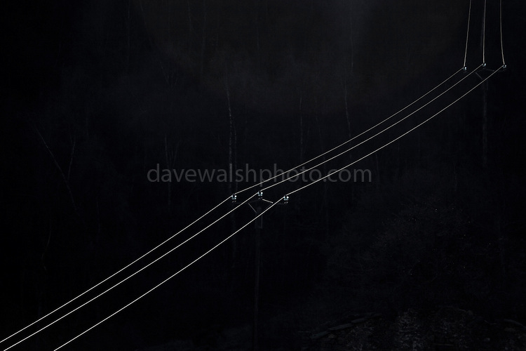 Sunlight falls on electrical transmission cables in a valley near the village of Py, in the Eastern Pyrenees, France.  Abstract ideas - electrical energy is synonymous with lighting homes; in this case, solar energy is falling on electrical cables containing a current probably generated by non-renewable means.