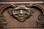 Wooden carved devil face in bench seat, Ufford church, Suffolk, England, UK