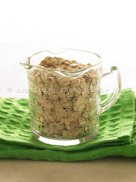 Glass measuring cup filled with uncooked oats.