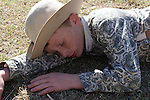 A young red head freckled country boy laying down on the ground resting