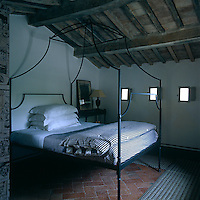 A bedroom of simple and rustic elegance is tucked under the eaves and the bed is a contemporary reproduction of a 19th century original
