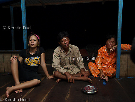"""Floating Lives on the Tonle Sap - evening on the """"veranda"""" or front of the floating house. After a long day the family is tired and prepares to sleep at 9pm."""