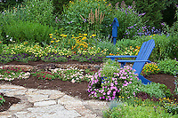 63821-21814 Flower garden with stone path, blue Adirondack chair and bird house. sedums, raspberry blast petunia and diamond frost euphorbia in blue pot, Butterfly Bushes, Joe Pye Weed (Eupatorium purpurea), Peach & Purple Verbenas, Yellow Lantana (Lantana camara), Karl Forster Grass, Marion Co., IL
