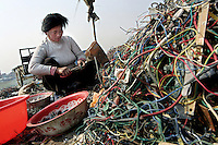 A migrant worker strips wires from e-trash in a junk yard in Guiyu in Guangzhou province.