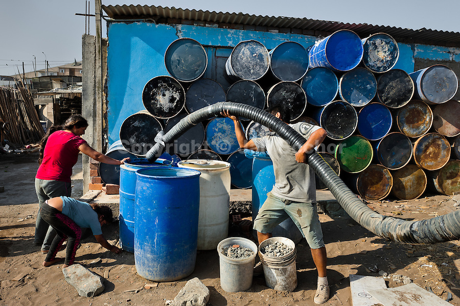 A Peruvian water distribution worker with a pipe fills plastic barrels with drinking water on the dusty hillside of Pachacútec, a desert suburb of Lima, Peru, 20 January 2015. Although Latin America (as a whole) is blessed with an abundance of fresh water, having 20% of global water resources in the the Amazon Basin and the highest annual rainfall of any region in the world, an estimated 50-70 million Latin Americans (one-tenth of the continent's population) lack access to safe water and 100 million people have no access to any safe sanitation. Complicated geographical conditions (mainly on the Pacific coast), unregulated industrialization (causing environmental pollution) and massive urban poverty, combined with deep social inequality, have caused a severe water supply shortage in many Latin American regions.