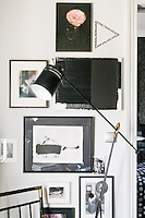 An elegant black angle poise lamp stands in one corner; behind a collection of artworks is displayed on the wall.