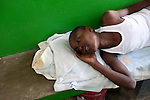 A cholera patient sleeps on a bench on Sunday, October 31, 2010 in Petite Riviere, Haiti.