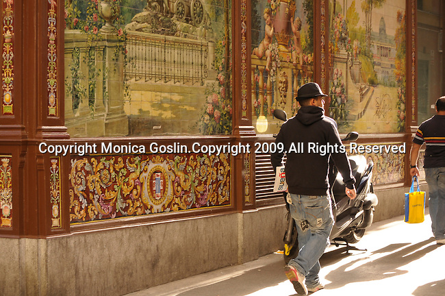 Two men walk by a motorcycle parked on a street with tiled walls in Madrid, Spain.