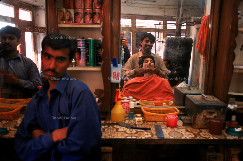 Barber shop, Lahore Pakistan... 4,800 years ago, at the same time as the early civilizations of Mesopotamia and Egypt, great cities arose along the flood plains of the Indus and Saraswati (Ghaggar-Hakra) rivers.  Developments at Harappa have pushed the dates back 200 years for this civilization, proving once and for all, that this civilization was not just an offshoot of Mesopotamia..They were a highly organized and very successful civilization.  They built some of the world's first planned cities, created one of the world's first written languages and thrived in an area twice as large as Egypt or Mesopotamia for 900 years (1500 settlements spread over 280,000 square miles on the subcontinent)..There are three major communities--Harappa, Mohenjo Daro, and Dholavira. The town of Harappa flourished during this period because of it's location at the convergence of several trade routes that spanned a 1040 KM swath from the northern mountains to the coast.