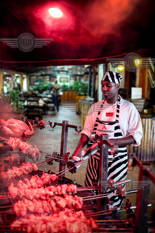 A chef cooking meats for lunch at Carnivore, a famous restaurant known for serving exotic meat alongside the usual chicken and beef.