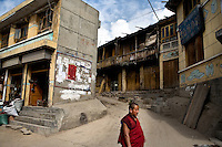 A Tibetan Buddhist monk walks past buildings in Xiahe, Gansu, China. Xiahe, home of the Labrang Monastery, is an important site for Tibetan Buddhists.  The population of the town is divided between ethnic Tibetans, Muslims, and Han Chinese.
