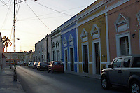 Late afternnon street in Merida, Yucatan Peninsula, Mexico, with cars and colorful buildings.